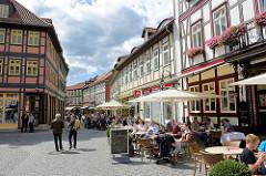 Fussgängerzone in Wernigerode - Fachwerkhäuser und Aussengastronomie - Tischen mit Gästen / Touristen in der Sonne /  Sonnenschirme; Westernstrasse in der Wernigeröder Altstadt.