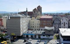 Blick vom Festungsberg auf Häuser der Stadt - historische Altbauten und schlichte Wohnblock, Kirchtürme der  Pfarrkirche Mariä Himmelfahrt - Kościół Wniebowzięcia Najświętszej Maryi Panny - errichtet ab 1390.