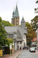 Blick durch den Hohen Weg in Goslar zum Gebäude Großes Heiliges Kreuz; errichtet 1254 als Hospiz - im Hintergrund die Kirchtürme der Marktkirche Sankt Cosmas und Damian.