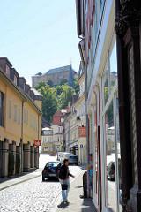 Tränkestrasse in Blankenburg - Blick zum Blankenburger Schloss und Kirchturm der St. Bartholomäus Kirche. Passanten auf der Strasse - Geschäfte.