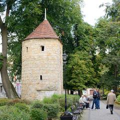 Historischer Verteidungsturm der Stadtbefestigung von Bolesławiec / Bunzlau; Grünanlage mit Holzbänken, Parkbesucher.
