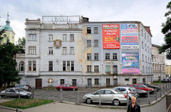 Mehrgeschossiges Mietshaus - Gründerzeitarchitektur; Reste einer alten Dachbeschriftung - großflächige Werbeplakate an der Hausfassade; links die Pfarrkirche Hl. Kreuz und Kreuzherrenkommend von Świdnica / Schweidnitz.