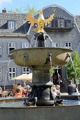 Romanischer Marktbrunnen auf dem Marktplatz in Goslar - Bronzeschale und vergoldeter Reichsadler, Brunnenadler. Dahinter der Giebel vom Kaiserringhaus.