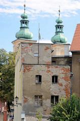 Alte Hausfassade, abbröckelnder Putz - freigelegte Ziegelsteine; Kirchtürme der Minoritenkirche St. Maria in  Kłodzko / Glatz.