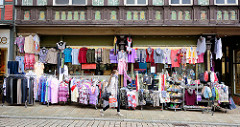 Modegeschäft mit Kleidung / Blusen + Pullover in der Auslage auf der Strasse - Lange Strasse, Blankenburg. Historisches Fachwerkhaus mit Malerei in der Gebälkfüllung.