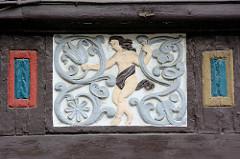 Schnitzerei im Fachwerk eines historischen Gebäudes in der Stadt Goslar; nackte Frau im Rankwerk.