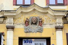 Relief - Stuckdekor; Eingang eines Wohnhauses in Świdnica / Schweidnitz; zwei Engel mit goldenen Flügeln halten das Schweißtuch der Veronika - Jesusportrait.