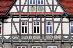 Hausfassade am Marktplatz von Goslar, Harz - Kerbschnitzereien am Fachwerk, farbige Rosetten - Inschrift Wo Gott nicht giebt zum Haus sein Gunst Da ist all unser Bau'n umsunst.