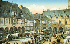 Historisches Bild vom Goslarer Marktplatz - lks. das Kaiser Worth, re. das Rathaus mit Blumen vor den Fenstern - Markttreiben auf dem Platz, Fuhrwerke mit Planen abgedeckt; Verkaufsstände mit Gemüse - Passanten.