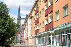 Wohnhäuser mit Balkons - Geschäfte im Erdgeschoss, Breiter Weg in Halberstadt - im Hintergrund die Türme der St. Martini Kirche.