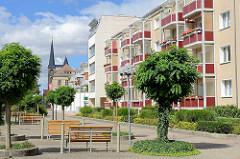 Wohnhäuser mit farblich verkleideten Balkons - Fussgängerzone mit Holzbänken, Breiter Weg in Halberstadt - im Hintergrund die Türme der St. Martini Kirche.