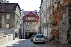 Architektur in  Kłodzko / Glatz; alte Hausmauer, abgebröckelter Putz - Gräser wachsen aus den Mauerfugen.