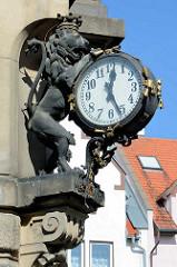 Bronzelöwe mit Krone hält eine grosse Straßenuhr - Fassadendekoration in  Kłodzko / Glatz.