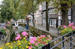 Lauf der Abzucht durch Goslar - gemauerter Flusslauf, am Geländer Blumenkästen mit blühenden Blumen / Geranien; Strasse mit Kopfsteinpflaster, Fachwerkhäuser.