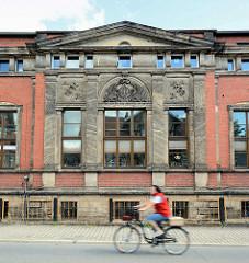 Historische Industriearchitektur in Blankenburg - Steinrelief im Giebel, Monogramm mit Rankwerk, Jahreszahl 1892 - schnell fahrende Radfahrerin.