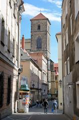 Kirchturm der der Katholische Pfarrkirche Mariä Himmelfahrt - Kościół Wniebowzięcia Najświętszej Maryi Panny in Glatz / Kłodzko - errichtet ab 1390. Schmale Gasse mit Fussgängern - Litfaßsäule.