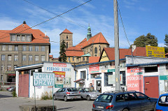 Rückseite, Kirchenschiff der Katholische Pfarrkirche Mariä Himmelfahrt - Kościół Wniebowzięcia Najświętszej Maryi Panny in Glatz / Kłodzko - errichtet ab 1390. Autowerkstatt mit bunten Schildern.