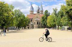 Ein Fahrradfahrer überquert den Domplatz von Halberstadt - im Hintergrund die Liebfrauenkirche; Ursprungsbau ab 1089.
