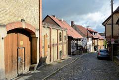 Strasse mit Wohnhäusern - Lagerhaus mit Ziegel-Mauerwerk, Toreinfahrt; Bürgersteig / Fussweg und Strasse mit Kopfsteinpflaster gepflastert.