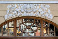 Oberlicht mit geschnitzten Fenstersprosse un Glassscheiben mit Facettenschliff - Stuckdekor / Rankwerk, Blattwerk; Architektur in Kłodzko, Glatz.