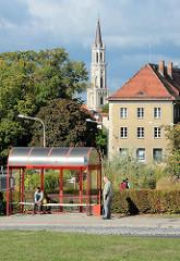 Bushaltestelle, wartende Fahrgäste in Bolesławiec / Bunzlau - im Hintergrund der Kirchturm der katholischen Maria-Hilf-Kirche.