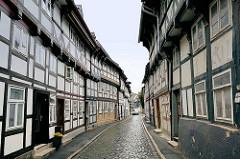 Schmale Strasse, Kopfsteinpflaster; Einbahnstrasse - ein Auto passt gerade auf die Fahrbahn - Fachwerkarchitektur in Goslar / Harz.