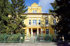 Klassizistische Architektur - gelbe Hausfassade mit weiss abgesetzten Relief / Dekorelementen - Kulturgebäude in Bunzlau / Bolesławiec.