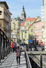 Fussgängerbrücke über die Glatzer Neisse in Kłodzko / Glatz; ein Schuljunge mit Ranzen überquert die Brücke - im Hintergrund der Rathausturm.