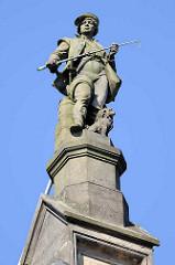 Steinfigur Fuhrmann / Kutscher mit Hund - Skulptur auf einem Dach am Zippelhaus in der Altstadt Hamburgs.