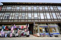 Lange Strasse, Blankenburg / Harz - Geschäftsstrasse der Stadt; Filiale Deutsche Bank, Modegeschäft mit Kleidung / Blusen + Pullover in der Auslage auf der Strasse. Historisches Fachwerkgebäude