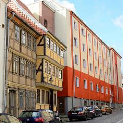 Historische Fachwerkarchitektur - schlichter Neubau mit teilw. orangenfarbene Fassade; Architektur in Blankenburg, Harz.