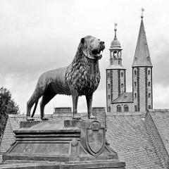 Braunschweiger Löwe vor der Kaiserpfalz in Goslar - im Hintergrund die Kirchtürme der Marktkirche Sankt Cosmas und Damian.