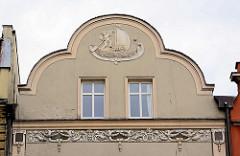 Giebelschmuck von einem Wohnaus in der  Altstadt von Świdnica / Schweidnitz;  eine Putte / Engel rudert eine Barke unter Segeln.