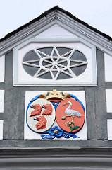 Schnitzerei im Dachgiebel, unter einer goldenen Krone Löwenköpfe mit ausgestreckter Zunge - Storch; Inschrift Anno 1773 - Hausfassade in Goslar / Harz.