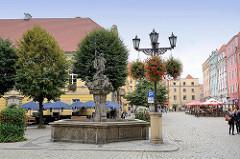 Neptunbrunnen - Historische Altstadt von Świdnica - Schweidnitz; Aussengastronomie - Sitzplätze unter Sonnenschirmen.