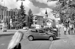 Strassenansicht in Bunzlau / Bolesławiec; parkende Autos - Passanten, im Hintergrund der Kirchturm der Pfarrkirche Mariä Himmelfahrt.