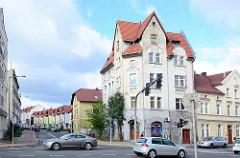 Architektur in Bunzlau / Bolesławiec - mehrstöckiges Gründerzeitgebäude mit Doppelgiebel, im Hintergrund Neubauten.