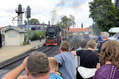 Lokomotive - Dampflokomotiven am Bahnhof Wernigerode - ein Zug der Schmalspurbahn fährt ab. Schaulustige / Touristen beobachten den Vorgang.