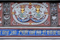 Schnitzerei im Fachwerk eines historischen Gebäudes in der Stadt Goslar - Namensinschrift Tile Reineken, Agneta Curds - Blütenoranamentick - Maskaron, Fratzengesicht mit Arabesken, Rankwerk Schnitzereien.