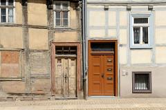 Alt + Neu, restauriertes Fachwerkhaus mit blau abgesetzten Fenstern und Fachwerkbalken, neue Holztür mit Briefkästen - altes FAchwerkhaus mit  vernagelten Fenster und alter Holztür, abgeblätterte Farbe. Architektur in Halberstadt.