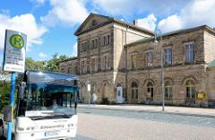 Altes Empfangsgebäude vom Bahnhof Blankenburg - stillgelegtes, geschlossenes Gebäude; Bussteig und wartender Personenbus.