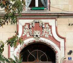 Dekorelemente über der Eingangstür eines Jugenstilgebäudes in Kłodzko / Glatz; Oberlicht mit geschwungenen Leisten gefasst - Bauschmuck mit farblich abgesetztem Maskaron und Jugendstil Blattwerk.