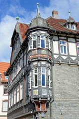 Erkerturm mit Schieferdach - geschnitzten Säulen, farbig gefasste Kerbschnitzerei - Rosetten; Schieferdach. Gebäude am Marktplatz in der Altstadt von Goslar / Harz.
