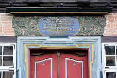 Lateinische Inschrift über dem Türsturz - Arabesken, Schnitzerei - Hausfassade in Goslar, Harz.