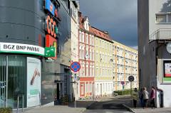 Moderne Metallfassade eines Geschäftshauses, Bankgebäude - mehrgeschossige Wohnhäuser, dunkler Regenhimmel in Bunzlau / Bolesławiec.