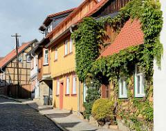 Fachwerkhäuser - Fassade mit Holz verkleidet, dicht mit Wein bewachsen - Kopfsteinpflaster; Wohnhäuser in Blankenburg / Harz.