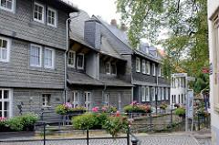 Lauf der Abzucht in Goslar - mit Schiefer verkleidete Hausfassaden - Blumenkasten mit Geranien am Brückengeländer.