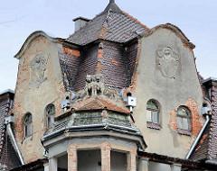 Giebel mit abbröckelndem Putz, Hundeskupturen - mehrgeschossiges Wohnhaus - Eckgebäude; Gründerzeitarchitektur in Świdnica / Schweidnitz.
