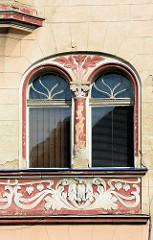 Jugendstil-Architektur in Kłodzko / Glatz; florales Stuckelement mit Säule - Arkanthusrelief mit Eule als Schmuckband auf der Hausfassade.