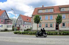 Siedlungshäuser mit Holz verkleidete Fassade - Motorrad auf der Halberstädter Strasse in Wernigerode.